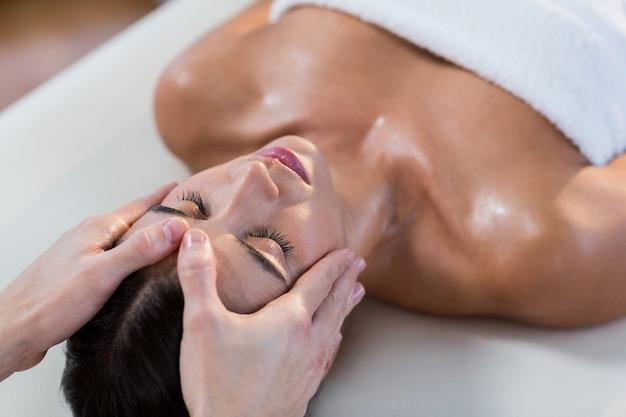 Mannelijke fysiotherapeut die hoofdmassage geeft aan vrouwelijke patiënt