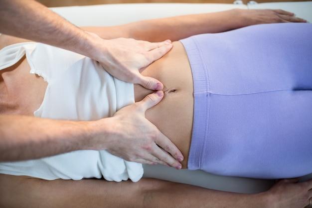 Mannelijke fysiotherapeut die maagmassage geeft aan vrouwelijke patiënt