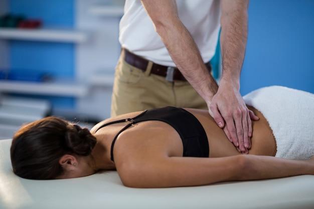 Mannelijke fysiotherapeut die massage teruggeven aan vrouwelijke patiënt