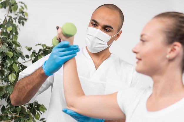 Mannelijke fysiotherapeut die met medisch masker de kracht van de vrouw controleert