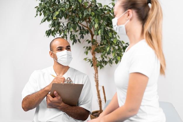 Mannelijke fysiotherapeut die met medisch masker en klembord vrouw controleert