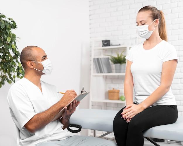 Mannelijke fysiotherapeut die met medisch masker vrouw controleert