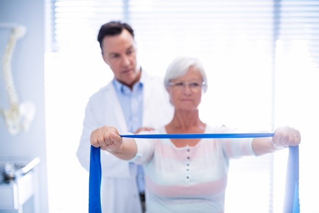 Mannelijke fysiotherapeut die schoudermassage geeft aan hogere vrouw
