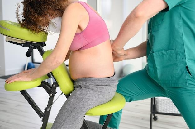 Mannelijke fysiotherapeut geneest rugpijn van een zwangere vrouw.