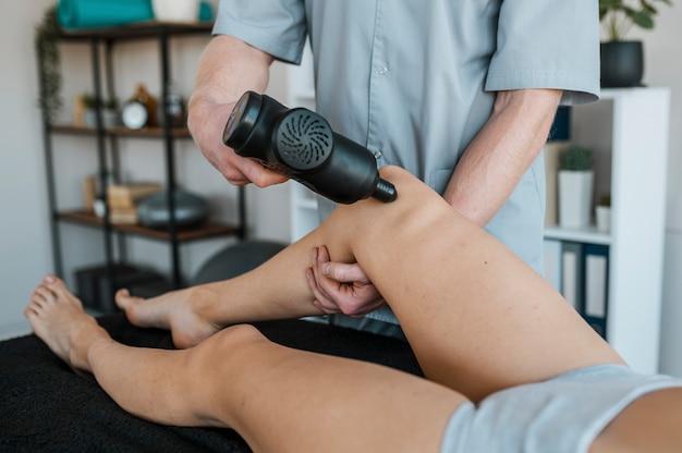 Mannelijke fysiotherapeut met behulp van apparatuur van vrouwelijke patiënt tijdens een fysiotherapie-sessie