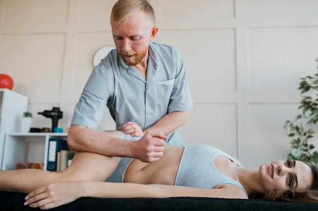 Mannelijke fysiotherapeut met vrouwelijke patiënt tijdens een kinesiologiesessie