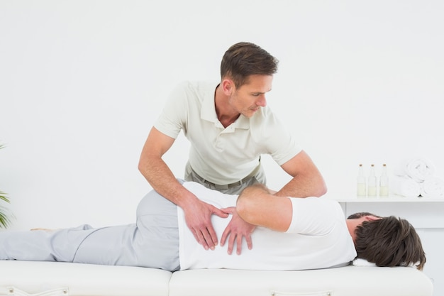 Mannelijke fysiotherapeut onderzoekt man terug