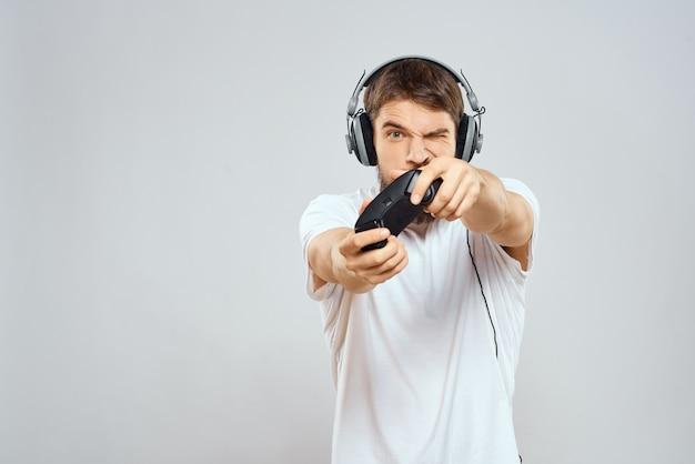 Mannelijke gamer die een console met joysticks in hoofdtelefoons speelt