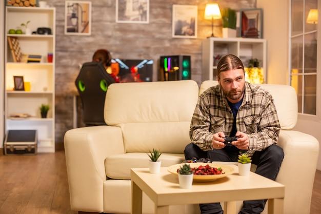 Mannelijke gamer die videogames speelt op een console in de woonkamer terwijl hij op de bank zit
