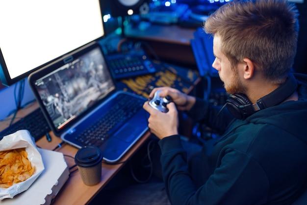 Mannelijke gamer in koptelefoon houdt joystick vast en speelt videogame op console of desktop-pc, gaming-levensstijl, cybersport. computerspelletjesspeler in zijn kamer met neonlicht, streamer