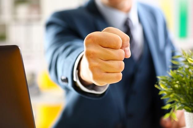 Mannelijke gebalde vuist in kostuum bij kantoorclose-up