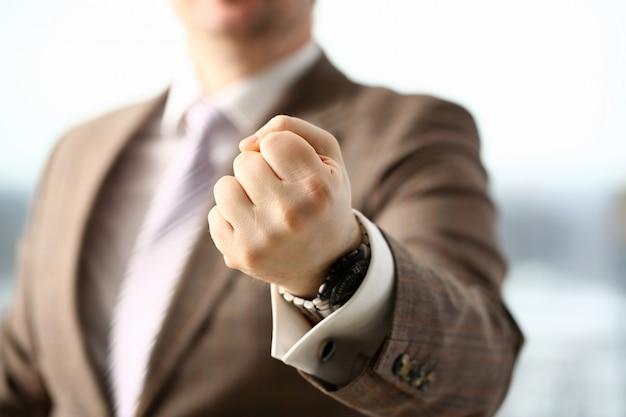 Mannelijke gebalde vuist in pak op kantoor