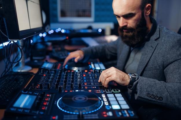 Mannelijke geluidseditor op afstandsbedieningspaneel in de opnamestudio.