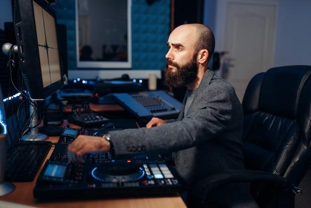 Mannelijke geluidsredacteur in de opnamestudio