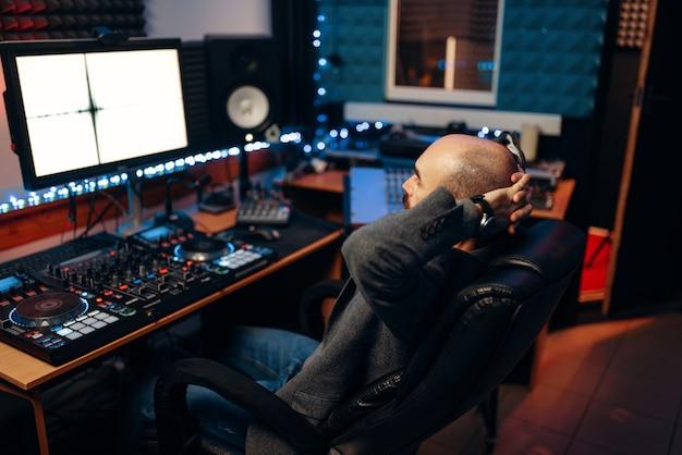 Mannelijke geluidstechnicus bij afstandsbediening, achteraanzicht
