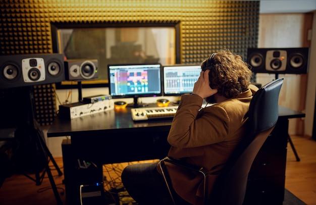 Mannelijke geluidstechnicus bij het mengen van consol, achteraanzicht, opnamestudio interieur op achtergrond. synthesizer en audiomixer, muzikantenwerkplek, creatief proces