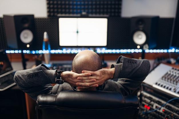 Mannelijke geluidstechnicus op afstandsbedieningspaneel, achteraanzicht, opnamestudio.