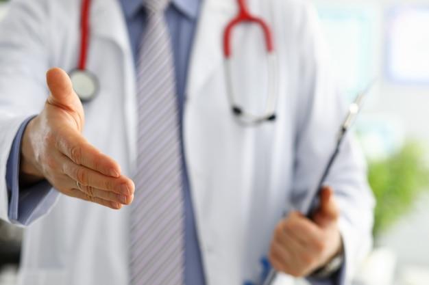 Mannelijke geneeskunde arts die hand aanbiedt om in bureauclose-up te schudden. groet en verwelkomend gebaar. medische genezing en tests advertentieconcept. arts klaar om de patiënt te onderzoeken