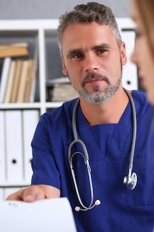 Mannelijke geneeskunde arts in blauwe uniform houden en voorschrift geven