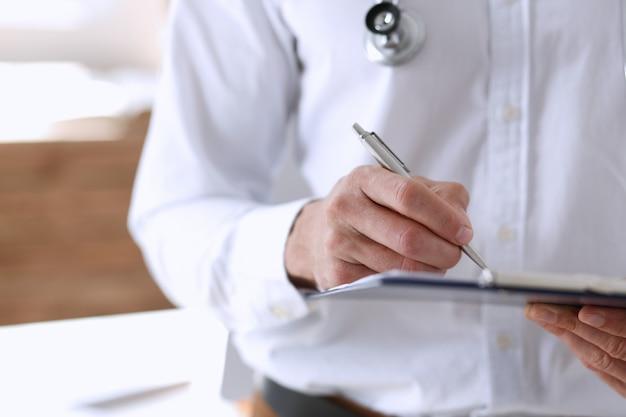 Mannelijke geneeskunde artsenhand die zilveren pen en klembordstootkussenclose-up houden.