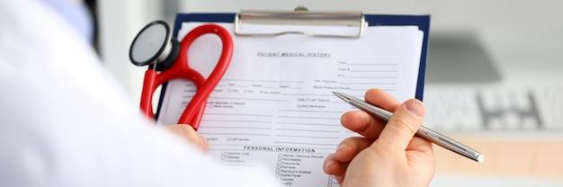 Mannelijke geneeskunde artsenhand die zilveren pen houden die iets schrijven op klembordclose-up. afdelingsronde, patiëntbezoekcontrole, medische berekening en statistiekenconcept. arts klaar om patiënt te onderzoeken