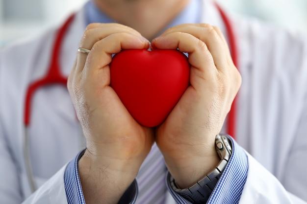 Mannelijke geneeskunde artsenhanden die en rood stuk speelgoed hart houden behandelen