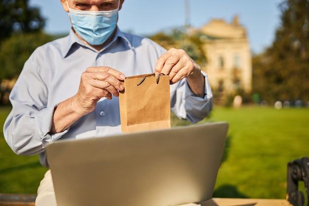Mannelijke gepensioneerde man zit in de stad met laptop