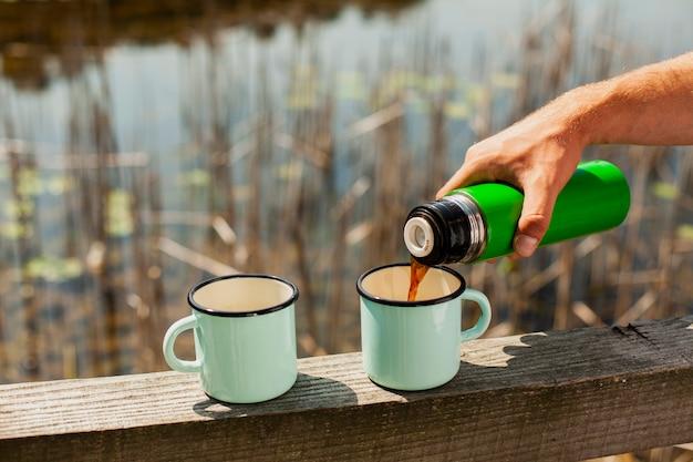 Mannelijke gietende drank in koppen bij rivier