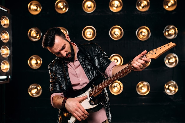 Mannelijke gitarist op het podium met decoraties van lichten