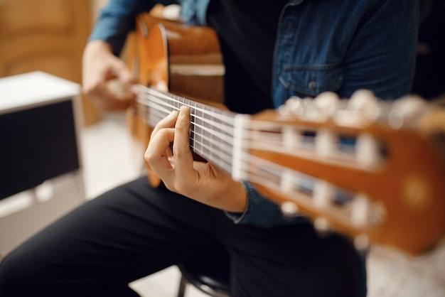 Mannelijke gitarist probeert te spelen op akoestische gitaar in muziekwinkel. assortiment in muziekinstrumentenwinkel, musicus die uitrusting koopt
