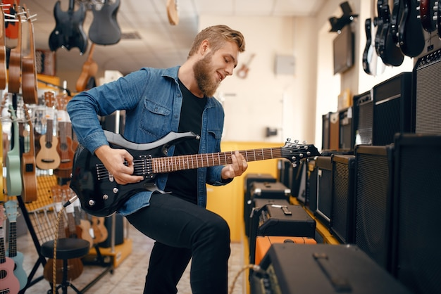 Mannelijke gitarist speelt op elektrische gitaar in muziekwinkel. assortiment in muziekinstrumentenwinkel, musicus die uitrusting koopt