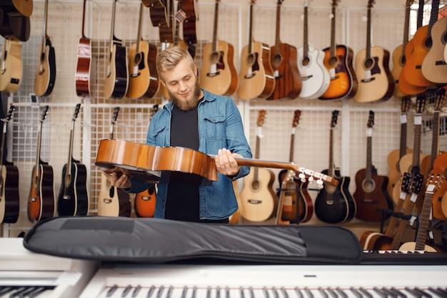 Mannelijke gitarist zet akoestische gitaar in de koffer in muziekwinkel. assortiment in muziekinstrumentenwinkel, musicus die uitrusting koopt