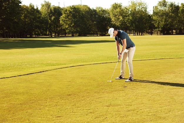Mannelijke golfspeler die golfbal op groen zet