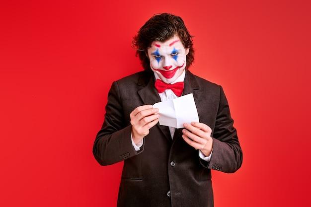 Mannelijke goochelaar die een truc met handen uitvoert die op rode achtergrond, met kleurrijke halloween-samenstelling op gezicht worden geïsoleerd