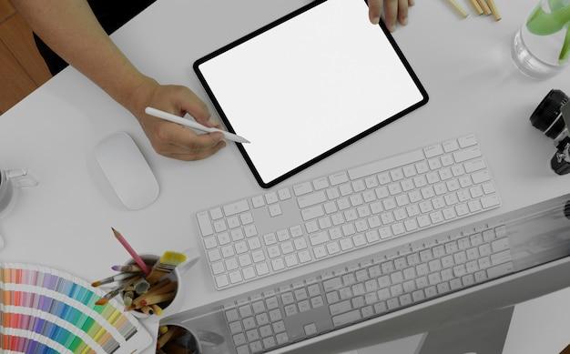 Mannelijke grafisch ontwerper puttend uit leeg scherm digitale tablet op wit bureau met computer, camera en designer benodigdheden