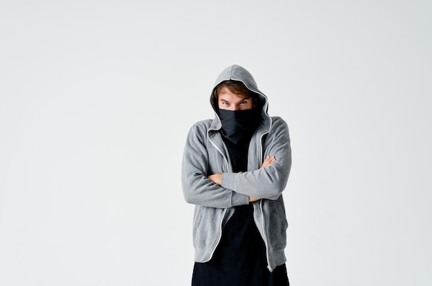 Mannelijke hacker in een grijze trui die zwart masker op zijn gezicht steelt