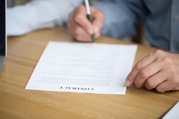 Mannelijke hand die contract ondertekent, hogere mens die handtekening op document zet