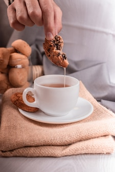 Mannelijke hand die een chocoladekoekje in de kop thee onderdompelt