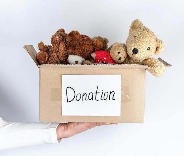 Mannelijke hand die een document bruine doos met het speelgoed van kinderen houdt