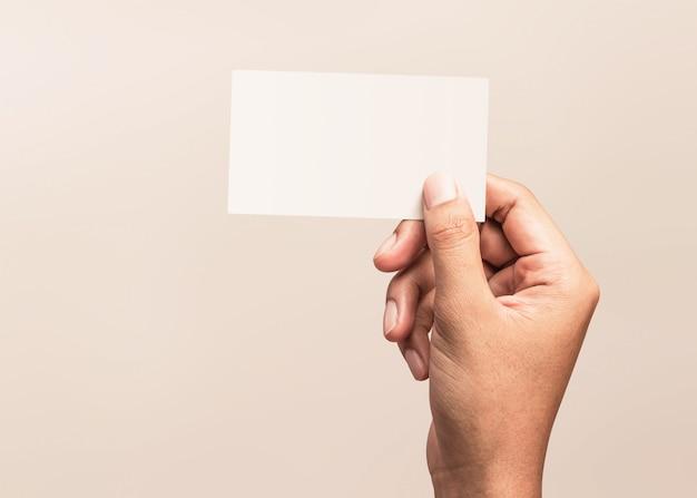 Mannelijke hand die een leeg adreskaartje op een grijze achtergrond voor tekst of ontwerp houdt