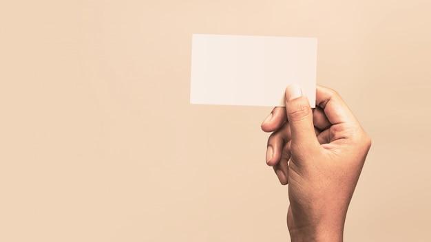 Mannelijke hand die een leeg adreskaartje op een uitstekende achtergrond voor tekst houdt.