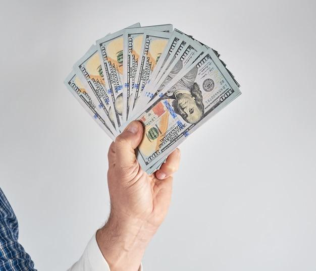 Mannelijke hand die een stapel van honderd dollarsrekeningen houdt
