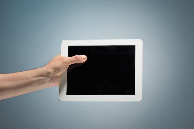 Mannelijke hand die een tablet houdt