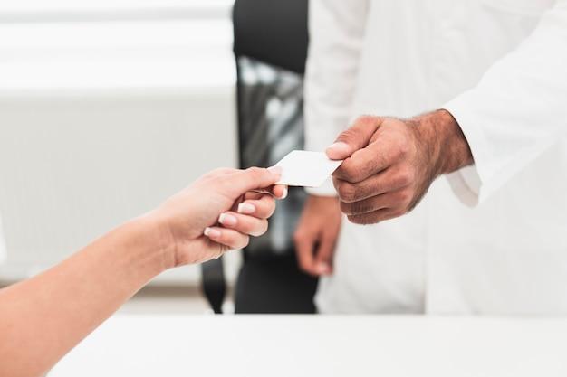 Mannelijke hand die een witte kaart geeft