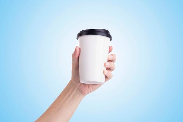 Mannelijke hand die een witte koffiekop geïsoleerd houdt