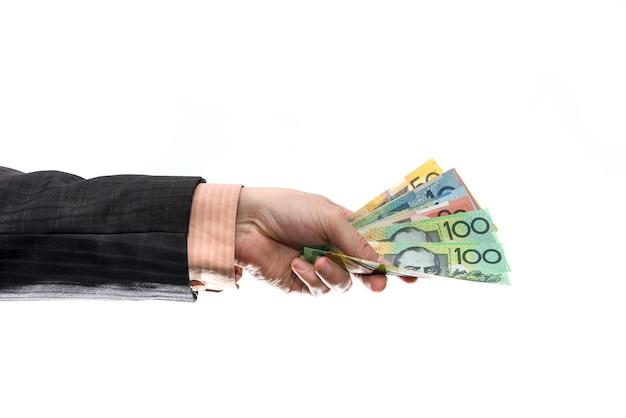 Mannelijke hand die en australische dollarbankbiljetten houdt