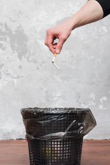 Mannelijke hand die gebroken sigaret binnen werpt aan de vuilnisbak