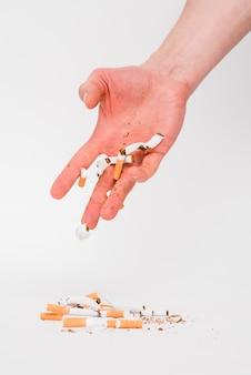 Mannelijke hand die gebroken sigaretten over witte achtergrond werpt