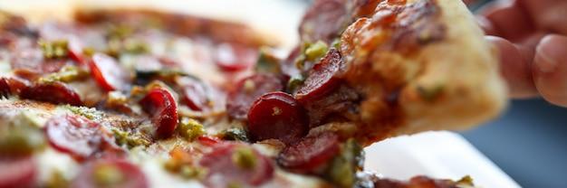 Mannelijke hand die groot stuk van smakelijk vers pizzaclose-up houdt