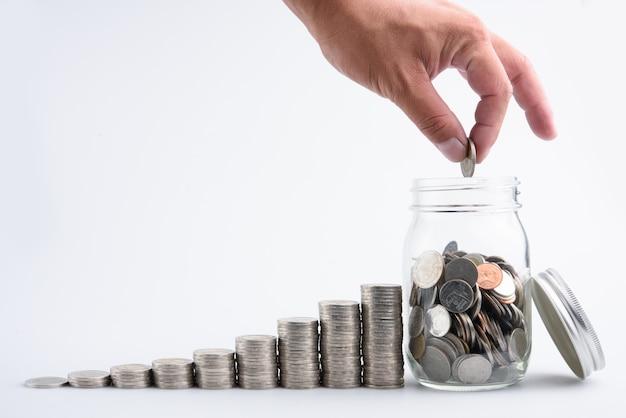 Mannelijke hand die muntstukken in kruik met van het de stap groeiend geld van de geldstapel het sparen geld, bu van conceptenfinanciën zetten
